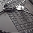 Stethoscope lying on the keyboard — Stock Photo