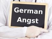 Doctor shows information on blackboard: german angst — Stock Photo