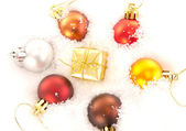 Christmas tree balls and gift in snow — Stock Photo