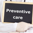 Doctor shows information on blackboard: preventive care — Stock Photo