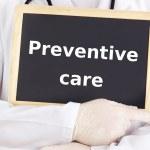 Doctor shows information on blackboard: preventive care — Stock Photo #17006943