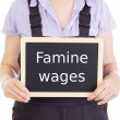 Craftsperson with blackboard: famine wages — Stock Photo