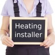 Craftsperson with blackboard: heating installer — Stock Photo
