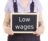 Craftsperson with blackboard: low wages — Stock Photo