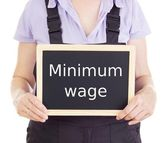 Craftsperson with blackboard: minimum wage — Stock Photo