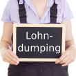 Stock Photo: Craftsperson with blackboard: social dumping
