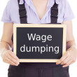 Craftsperson with blackboard: wage dumping — Stock Photo #17881647