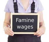 Craftsperson with blackboard: famine wages — Stockfoto