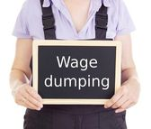 Craftsperson with blackboard: wage dumping — Stock Photo