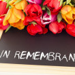 Bunch of tulips with blackboard: in remembrance - Stock Photo