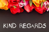 Bunch of tulips with blackboard: kind regards — Stock Photo
