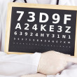 Stock Photo: Ophthalmologist holding blackboard with eyesight test