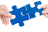 People putting two pieces of jigsaw together — Stock Photo