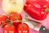 Preparing lunch with red peppers onions and tomatoes — Stock Photo