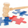 Wooden gavel hitting colourful puzzle pieces — Stock Photo #32116189