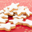 Many star shaped cinnamon biscuits on red background with golden stars — Stock Photo