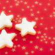Shining star shaped cinnamon biscuits on red background with golden stars — Stock Photo