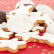 Mixed christmas biscuits on red background with golden stars — Stock Photo