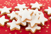 Star shaped cinnamon biscuits on red background with golden stars — Stock Photo