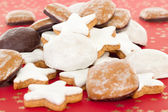 Mixed christmas cookies on red background with golden stars — Stock Photo