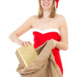 Smiling Mrs. Claus with jute bag and golden gift — Stock Photo #37573471
