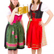 Beautiful women in dirndl drinking double beer at bavarian feast — Stok fotoğraf