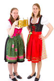 Beautiful women in dirndl drinking double beer at bavarian feast — Stock Photo