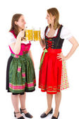 Beautiful girls in dirndl clinking their glasses — Stock Photo