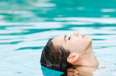 Woman relaxing in swimming-pool — Stock fotografie