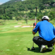 Stock Photo: Golf player with putter squatting to analyze green at golf c
