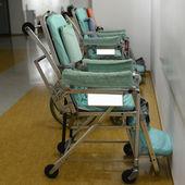 Empty wheelchair parked in hospital hallway — Stock Photo