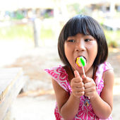 Cute little girl eating a lollipop in summertime — Stock Photo