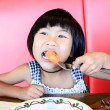 Girl eating fish finger — Stock Photo