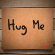 Stock Photo: Hug me message on paper and wooden wall