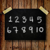 Number on message note with wooden background — Stockfoto