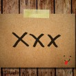 Note paper and clothes peg on a wooden background with kiss mess — Stock Photo #27423105