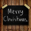Merry Christmas on message note with wooden background — Stock Photo