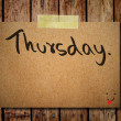 Thursday on note paper with wooden background — Stock Photo