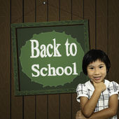 Happy Asian girl standing in front of Back to school green board — Stock Photo