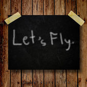 Let's fly on message note with wooden background — Stockfoto