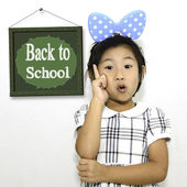 Asian girl pointing back to school on white background — Stock Photo