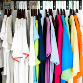 Colorful t-shirt on hangers — Stock Photo