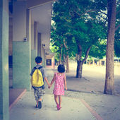 Boy and girl walking in the school with holding their hands in v — Stock Photo