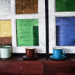 Old, vintageglass ware against a stain glass wall  — Stock Photo