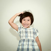 Happy Asian girl scratching her head and smiling — Stock Photo