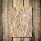Old crumpled paper on brown wood texture with natural patterns — Stock Photo