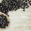 Stock Photo: Coffee beans on wooden ladle with wooden background