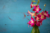 Purple orchid flowers in green vase with wooden wall — Stock Photo