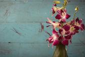 Violeta orquídeas flores en florero verde con pared de madera — Foto de Stock