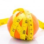 Orange with yellow measuring tape wrapped around it. On a white — Stock Photo #33141587